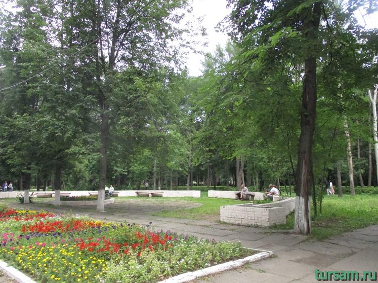 Лавочки для отдыха среди деревьев напротив клумбы с цветами в парке М.И. Калинина в городе Королев