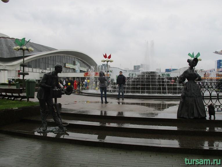 Скульптуры «Дама с собачкой» и «Фотограф» напротив фонтана возле Комаровского рынка в Минске